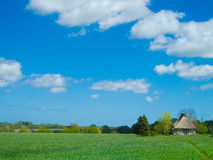 Ancient farmhouse with thatched roof in the fields Royalty Free Stock Photo