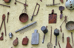 Ancient farming tools hanging on the wall of the House Royalty Free Stock Photo