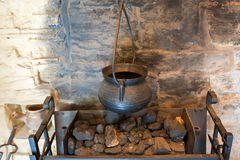 Ancient fireplace details. Details of the ancient fireplace in the medieval rustic cottage with old metal pot hanging over coals Stock Photography