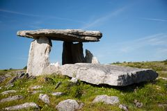 Preshistoric stone temple, megalit columns and roof, Poulnabrone dolmen in Ireland. Ancient flat stone hut on top of a grass covered hill, under sunlight in Stock Images