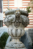 Ancient flower pot holder made from brute stone - very old sculpture with scarry face - gothic style. Ancient flower pot holder made from brute stone - very old stock images