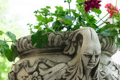 Ancient flower pot holder made from brute stone. very old sculpture with scarry face - gothic style. Ancient flower pot holder made from brute stone - very old stock image
