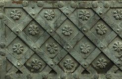 Ancient forged metal texture with decorative overlays. Doors, gates, shutters. Detail of a medieval gray door with metal decoratio. N, background, close-up royalty free stock images