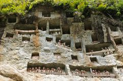 Ancient forged tombs in rock guarded by puppets. Londa, is a burial cave at the base of a massive cliff face.The entrance to the cave is guarded by a balcony of royalty free stock photos