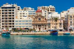 Ancient fortifications of Silema, Malta. Quay of Silema with traditional Maltese church with red dome in the sunny day, Valletta, Capital city of Malta Stock Photos