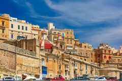 Ancient fortifications of Valletta, Malta. Quay of Valletta with traditional Maltese building with colorful shutters and balconies in the sunny day, Valletta Stock Photos