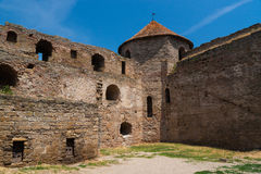 Ancient fortress wall with a round tower. Stock Photos