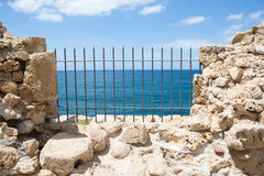 Ancient fortress wall with sea view through the grill Stock Photography