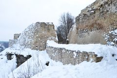 Ancient fortress wall and tower covered with snow, the wall is made of stone and limestone royalty free stock image