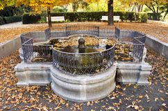 Ancient fountain in  autumn park with decorative fence Stock Photography