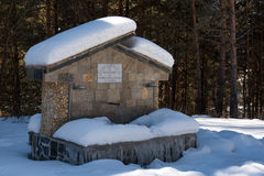 Ancient fountain with bench covered from snow at the forest during the winter, Bulgaria Royalty Free Stock Photos