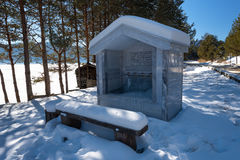 Ancient fountain with bench covered from snow at the forest during the winter, Bulgaria Stock Photography