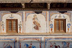 Ancient fresco with fade patterns, woman and Indian guards of historical wall Stock Photos