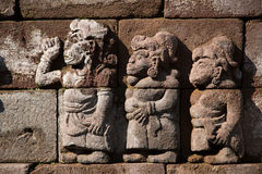 Ancient fretwork, stone carving on Indonesian temple. Old carved body carving on bricks of an antique building Stock Image