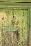Ancient front door with light green painted plaque royalty free stock image