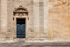 Ancient gate door and old wall. Ancient gate of old wall. In the famous square of Lecce, building the Basilica Church of the Holy Cross. Lecce, Italy Stock Images