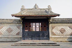 Ancient gate with latticed door leaves and embossed enclosure Stock Images