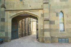 Ancient gate and an old wall with a window. In the street stock photography