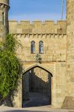 Ancient gate and an old wall with a window. In the street royalty free stock image