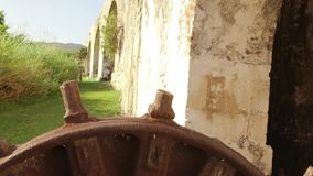 Ancient gear wheel sitting next to 18th century aqueduct Montego Bay, Jamaica stock footage