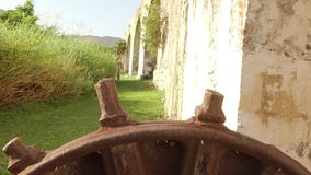 Ancient gear wheel sitting next to 18th century aqueduct Montego Bay, Jamaica. Aqueduct gear wheel located on a legendary 18th-century sugar plantation in stock footage