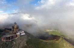 Ancient Gergeti Trinity Church high in the Caucasus mountains, aerial view. Georgia royalty free stock image