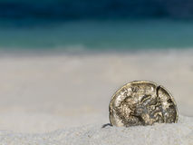 Ancient gold coin. On white sand beach, closeup Royalty Free Stock Image