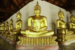 Ancient golden buddhas in the Thai buddha temple church.  stock photo