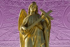 Golden sculpture of angel with cross. Ancient golden sculpture of angel with cross in hands Stock Photo