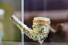Ancient golden smoking pipe in precious stones. Kuala Lumpur, Malaysia - February 11, 2016: Ancient golden smoking pipe in precious stones at the Islamic Arts Stock Image