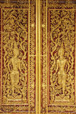Ancient golden wooden door of Thai temple Stock Photo