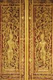 Ancient golden wooden door of Thai temple Stock Photo
