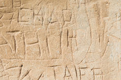 Ancient Graffiti. Old Scratched Graffiti in Sandstone Brick Royalty Free Stock Photo