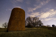 Ancient Grain Silo at Night. A Brick grain silo that is about to fall over stock image