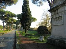 Ancient grave on the ancient Appian Way to Rome in Italy. White grave on the right with white statues inside of niche. Marble statues of busts and heads of men Royalty Free Stock Images