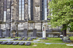 Ancient grave sites marked by horizontal headstones at the foot of Cologne Cathedral. A peaceful area at the base of the ancient Catholic Church stock images