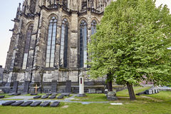 Ancient grave sites marked by horizontal headstones at the foot of Cologne Cathedral. Cologne`s iconic religious landmark royalty free stock photos