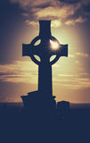 Ancient Graveyard At Sunset. Vintage Style Image Of Sun Glinting Through A Celtic Cross Gravestone Stock Photography