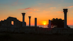 Ancient Greek basilica and marble columns in Chersonesus Taurica on the sunset background. Stock Photography