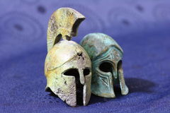 Ancient Greek battle helmets. Close up of two models of ancient Greek battle helmets, blue background Royalty Free Stock Image