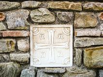 Ancient Greek Cross made of Marble on the Stone Wall Stock Image