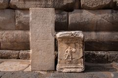 Ancient greek inscription and gladiator figure on block stones from Ephesus, Turkey royalty free stock photo