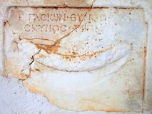 Ancient Greek Marble Fragment With Inscription. An Ancient Greek marble fragment, embedded in a rendered wall, with an Ancient Greek inscription and a bas relief Royalty Free Stock Photography