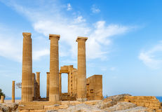 Ancient Greek pillars at Lindos acropolis with blue cloudy sky in the background Stock Photo