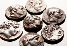 Ancient greek silver coins on reflective surface Royalty Free Stock Photography