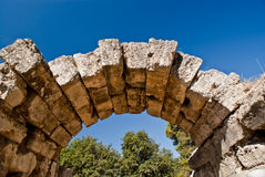 Ancient Greek stone arch at Olympia. Ancient Greek restored dry stone, unmortared, stone arch at Olympia with deep blue mediterranean sky Royalty Free Stock Photography