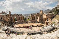 Ancient greek theatre. TAORMINA - OCTOBER 6: Tourists visit the ancient greek theatre of Taormina in Sicily, the main attraction of the city. October 6, 2014 royalty free stock photos