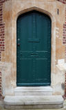 Ancient green door in a stone frame Stock Images