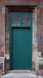 Ancient green door in a stone frame Stock Photos