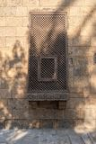 Ancient grunge wall with oriel window covered by interleaved wooden grid Mashrabiya. Cairo, Egypt Stock Image